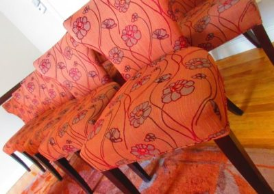 Group of crate & barrel dining chairs wearing floral textile